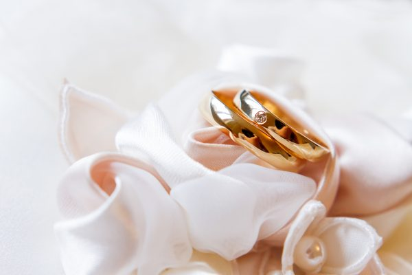 Golden wedding rings with diamond on silk fabric. Wedding jewelry details.